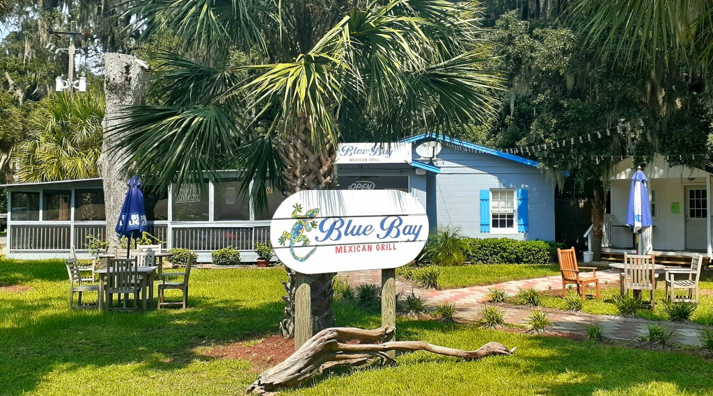 """Wooden sign reading """"Blue Bay Mexican Grill"""" with lizard painted on."""